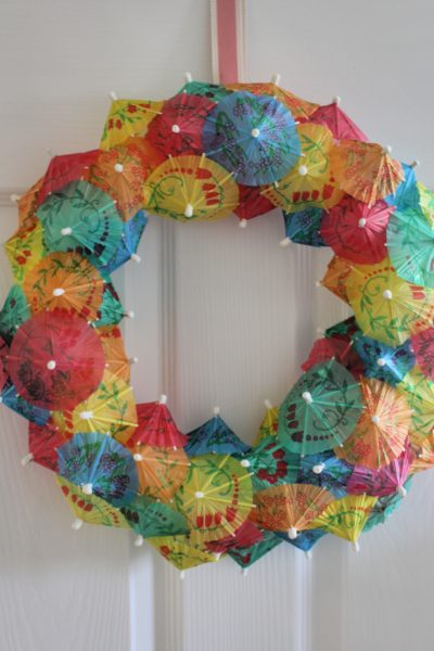 If you need an idea for a summer or spring wreath, you can't go far wrong with this one. It's great for your front door or to welcome your guests at a summer party. This wreath is bursting with colour! With just a box of umbrellas and a polystyrene ring it's perfect for new crafters. Not a hot glue gun or complicated craft materials in sight. Check out how you can make your own on a budget!