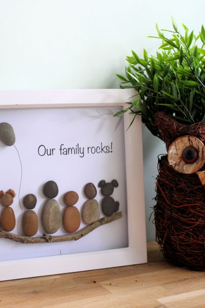 """Ever seen an idea and know you can totally make this yourself? Well, this pebble art """"our family rocks"""" picture was one of them. A simple DIY project for your home. And on a budget too! Check out the """"how to"""" on creating your own rock picture in no time."""