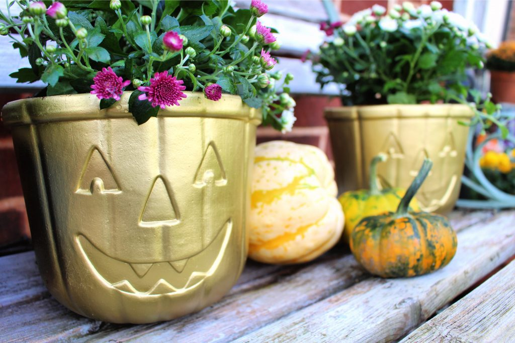 """Our kids are all grown up and their """"trick or treat"""" Halloween days are well and truly behind them.  So these treat buckets were in the loft gathering dust.  Until now - turns out they were a quick, simple and budget way to add some autumn fun to our front garden.  With some spray paint and some basic tools you can turn your kids old Halloween buckets into some quirky fun planters #Halloween #fall #autumn #autumn decor #fall decor #fall fun #autumn fun #autumn planters"""